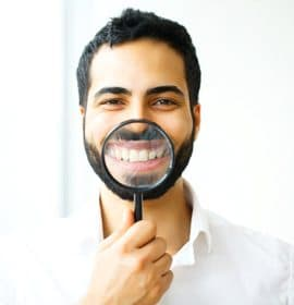 man holding magnifying glass to his smile