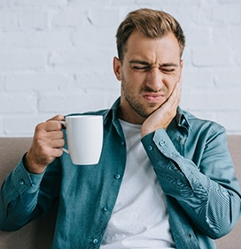 Man on couch with coffee rubbing his toothache