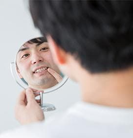 Man looking at his smile in the mirror