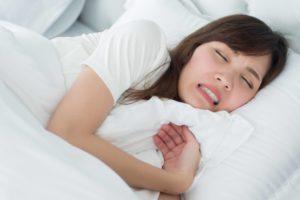 woman in bed grinding teeth while sleeping
