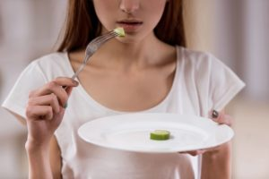 Woman hesitating to eat vegetable
