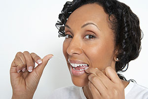 woman flossing her teeth before bed brampton dentist